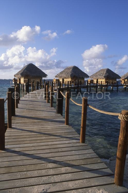 Islands;ocean;palm trees;blue;water;sky;manihi;french polynesia;pier;huts